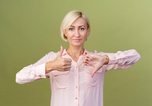 Tevreden jonge blonde slavische vrouw met haar duimen op en neer