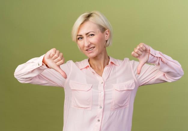 Tevreden jonge blonde slavische vrouw wijst naar zichzelf