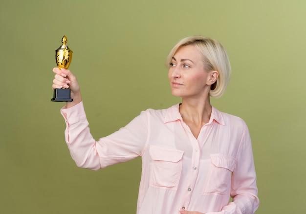 Tevreden jonge blonde slavische vrouwenholding en het bekijken winnaarbeker