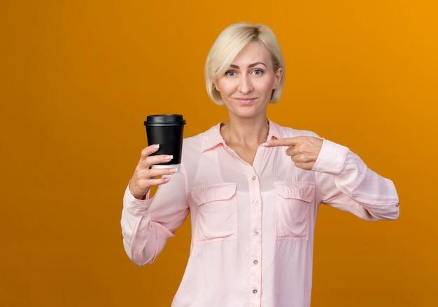 Tevreden jonge blonde slavische vrouwenholding en wijst naar politieagent van koffie die op oranje muur wordt geïsoleerd
