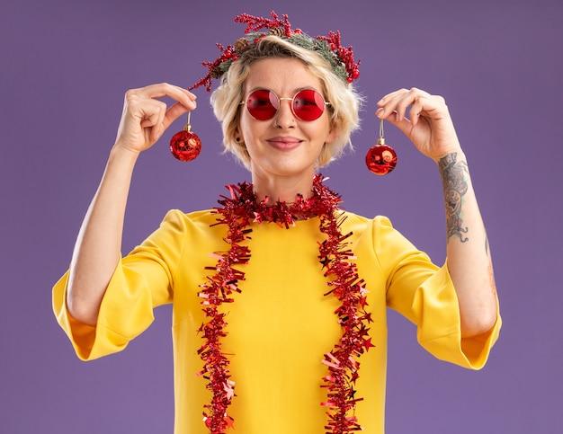Tevreden jonge blonde vrouw die de hoofdkroon van kerstmis en klatergoudslinger om hals draagt die kerstballen dichtbij hoofd houdt die geïsoleerd op paarse muur kijken