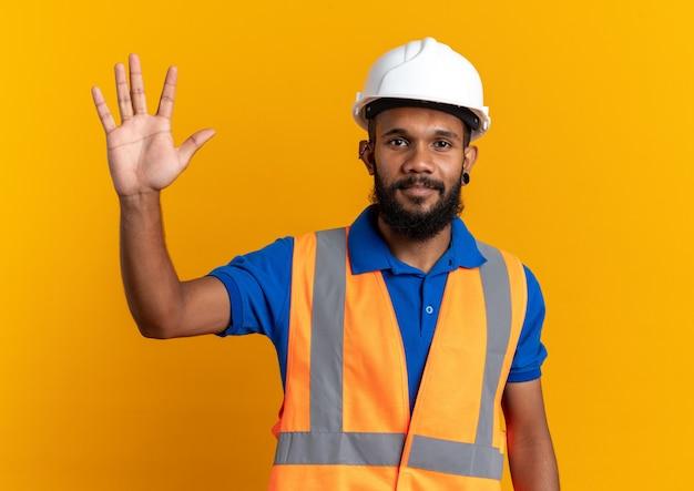 Tevreden jonge bouwer man in uniform met veiligheidshelm staande met opgeheven hand geïsoleerd op oranje muur met kopieerruimte