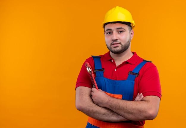 Tevreden jonge bouwersmens in eenvormige bouw en veiligheidshelm met gekruiste handen op de moersleutel van de borstholding die zelfverzekerd kijkt