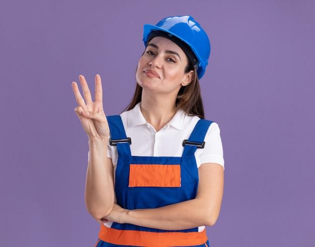Tevreden jonge bouwersvrouw in eenvormig die drie toont die op purpere muur worden geïsoleerd