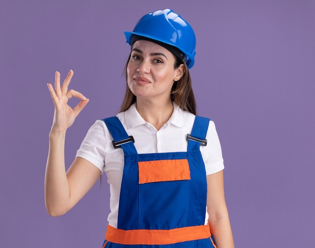 Tevreden jonge bouwersvrouw in eenvormig die ok gebaar toont dat op purpere muur wordt geïsoleerd