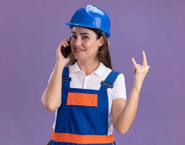 Tevreden jonge bouwersvrouw in uniform spreekt over telefoon en toont geitgebaar dat op purpere muur wordt geïsoleerd