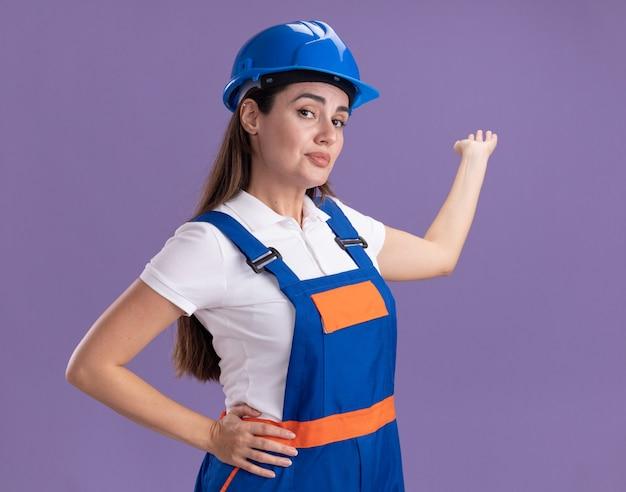 Tevreden jonge bouwersvrouw in uniforme punten met hand op achter geïsoleerd op paarse muur met exemplaarruimte