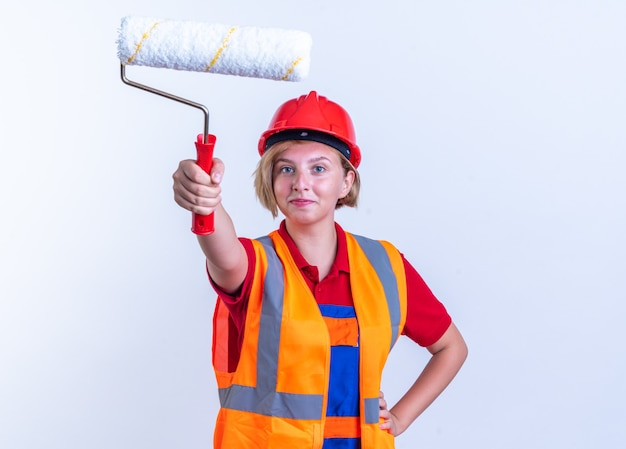 Tevreden jonge bouwvrouw in uniform die de rolborstel aan de voorkant vasthoudt en hand op de heup zet die op een witte muur wordt geïsoleerd