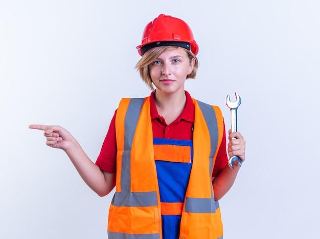 Tevreden jonge bouwvrouw in uniform met steeksleutelpunten aan de zijkant geïsoleerd op een witte muur met kopieerruimte