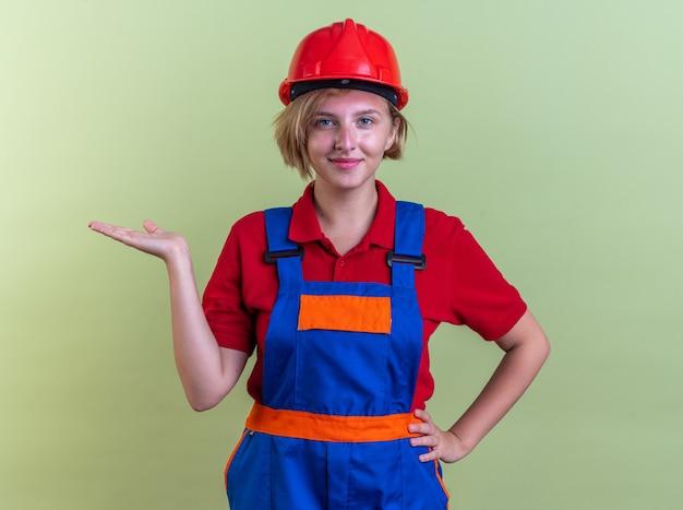 Tevreden jonge bouwvrouw in uniforme punten met de hand aan de zijkant geïsoleerd op olijfgroene muur met kopieerruimte