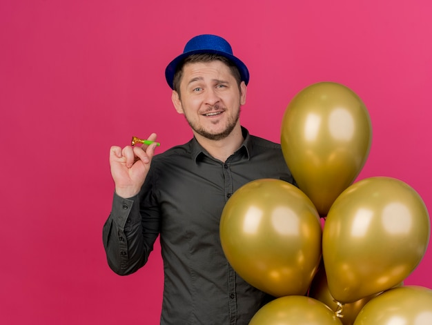 Tevreden jonge feestmens die blauwe hoed draagt die ballonnen met feestventilator houdt die op roze wordt geïsoleerd