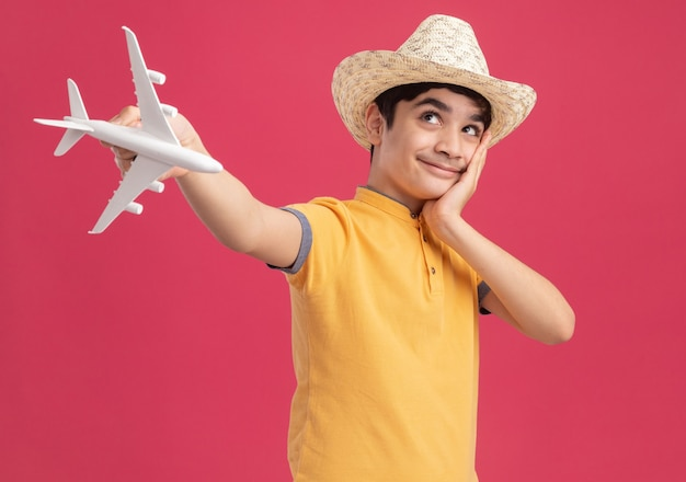 Tevreden jonge jongen met een strandhoed die het modelvliegtuig naar voren uitstrekt en zijn hand op zijn gezicht legt en omhoog kijkt geïsoleerd op roze muur