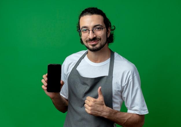 Tevreden jonge kaukasische mannelijke kapper die eenvormig en glazen draagt die mobiele telefoon houdt en duim toont die omhoog op groene achtergrond wordt geïsoleerd