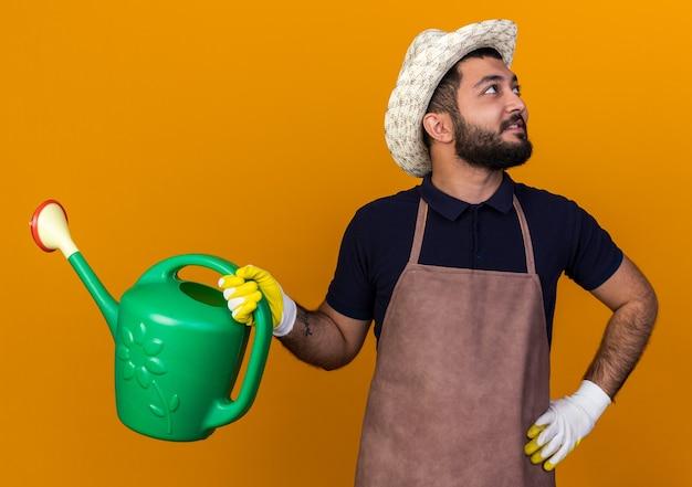 Tevreden jonge kaukasische mannelijke tuinman die tuinhoed en handschoenen draagt die gieter houden die naar kant kijken geïsoleerd op oranje muur met exemplaarruimte