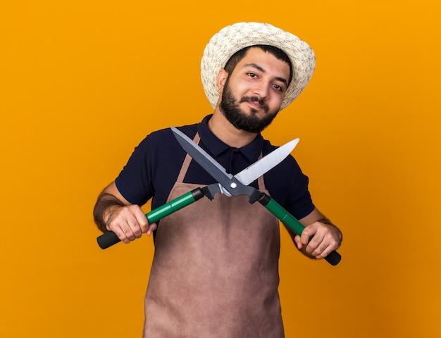 Tevreden jonge kaukasische mannelijke tuinman die tuinierende hoed draagt die tuinierende schaar houdt die op oranje muur met exemplaarruimte wordt geïsoleerd