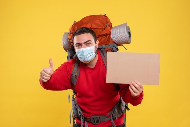 Tevreden jonge kerel die een medisch masker met rugzak draagt en een laken vasthoudt zonder te schrijven en een goed gebaar maakt op een geïsoleerde gele achtergrond