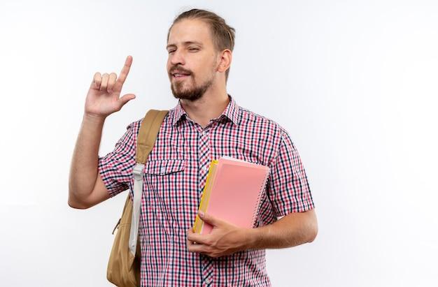Tevreden jonge kerelstudent die rugzak draagt die boekenpunten op omhoog houdt geïsoleerd op witte muur