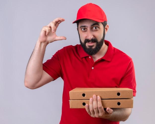 Tevreden jonge knappe bezorger die rode uniform en pet draagt die pizzadozen houdt en grootte toont die op witte muur wordt geïsoleerd