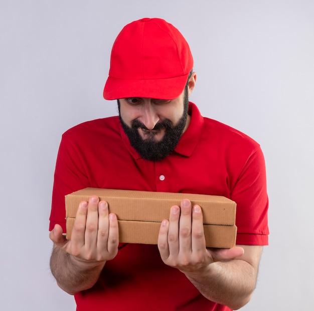 Tevreden jonge knappe bezorger die rode uniform en pet draagt en pizzadozen bekijkt die op witte muur worden geïsoleerd