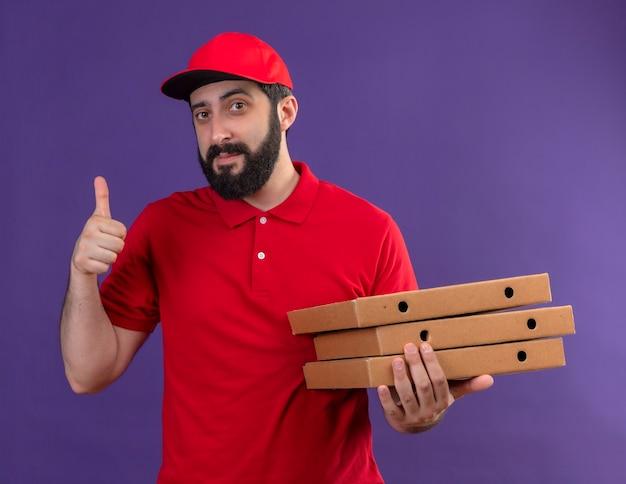 Tevreden jonge knappe bezorger die rood uniform en pet draagt die pizzadozen houdt en duim toont die op purpere muur wordt geïsoleerd