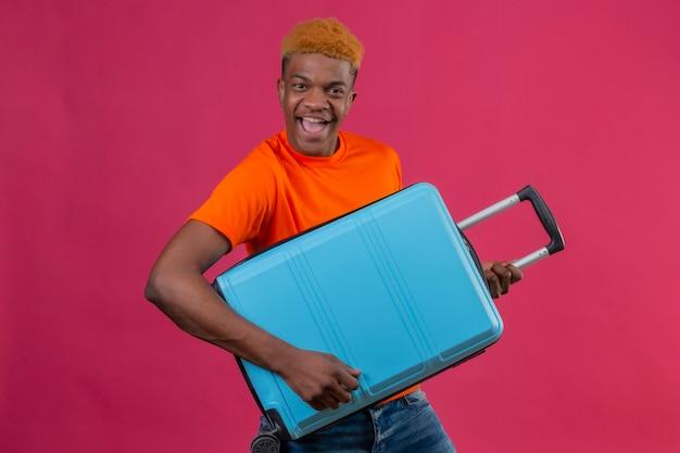 Tevreden jonge knappe jongen die de oranje reiskoffer van de t-shirtholding draagt