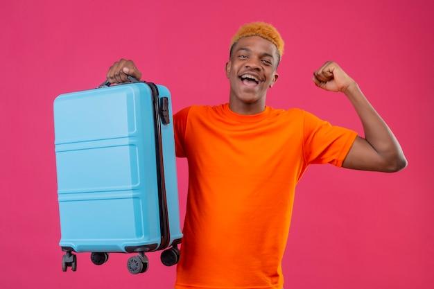 Tevreden jonge knappe jongen die een oranje t-shirt draagt en een reiskoffer vasthoudt glimlachend blij en opgewonden vuist heffen verheugend zijn succes staande over roze muur