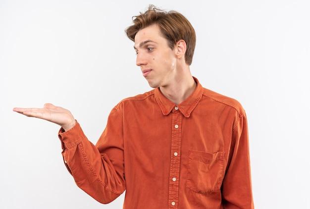 Tevreden jonge knappe kerel die een rood overhemd draagt dat doet alsof hij iets vasthoudt en kijkt naar iets dat op een witte muur is geïsoleerd