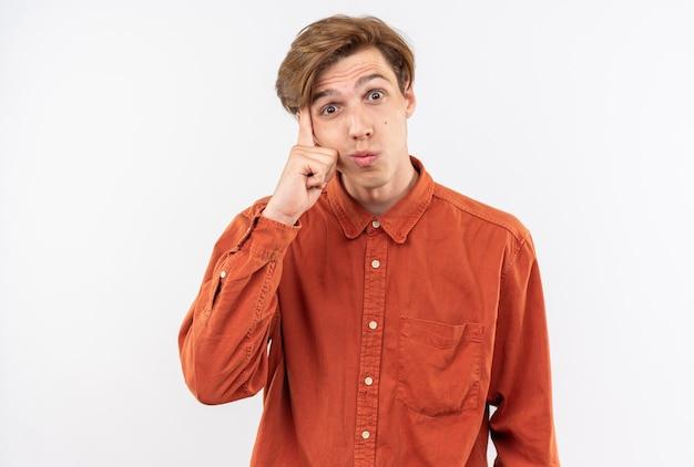 Tevreden jonge knappe kerel die een rood overhemd draagt dat vinger op wang zet