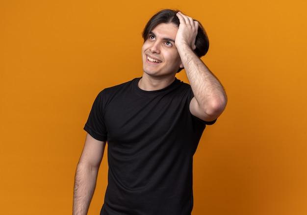 Tevreden jonge knappe kerel die een zwart t-shirt draagt, grijpt het hoofd geïsoleerd op een oranje muur