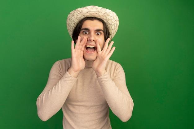 Tevreden jonge knappe kerel die voor het dragen van hoed kijkt die iemand roept die op groene muur met exemplaarruimte wordt geïsoleerd