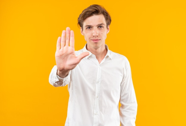 Tevreden jonge knappe kerel die wit overhemd draagt dat stopgebaar toont dat op oranje muur wordt geïsoleerd