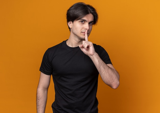 Tevreden jonge knappe kerel met een zwart t-shirt met een stiltegebaar geïsoleerd op een oranje muur met kopieerruimte