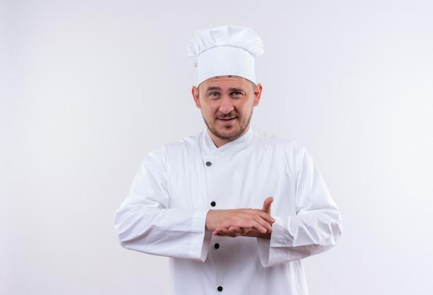 Tevreden jonge knappe kok in eenvormige chef-kok die handen samen geïsoleerd op witte ruimte houdt