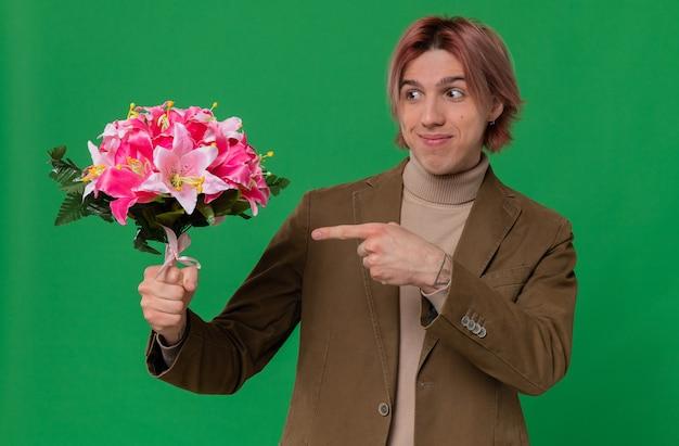 Tevreden jonge knappe man die een boeket bloemen vasthoudt en wijst