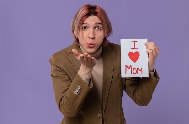 Tevreden jonge knappe man die een brief voor zijn moeder vasthoudt en een kus stuurt