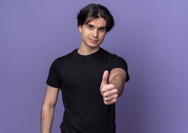 Tevreden jonge knappe man met een zwart t-shirt met duim omhoog geïsoleerd op een paarse muur