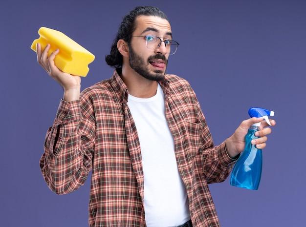 Tevreden jonge knappe schoonmaakster die de spuitfles van de t-shirtholding met spons draagt die tong toont die op blauwe muur wordt geïsoleerd