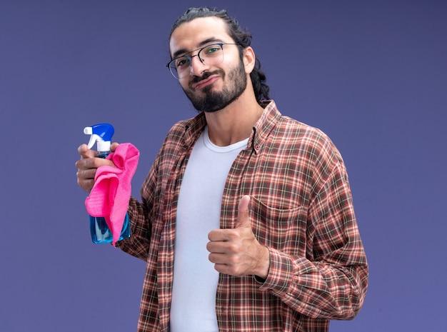 Tevreden jonge knappe schoonmaakster die de spuitfles van de t-shirtholding met vod draagt die duim toont die omhoog op blauwe muur wordt geïsoleerd