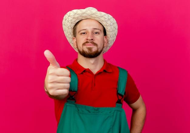 Tevreden jonge knappe slavische tuinman in uniform en hoed op zoek naar duim