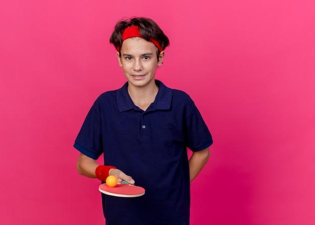 Tevreden jonge knappe sportieve jongen die hoofdband en polsbandjes draagt, pingpongracket met bal erop houdt, hand achter rug geïsoleerd houdt