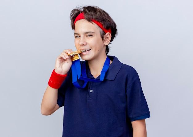 Tevreden jonge knappe sportieve jongen die hoofdband en polsbandjes met beugels en medaille om de nek draagt en naar kant bijtmedaille kijkt die op witte muur wordt geïsoleerd