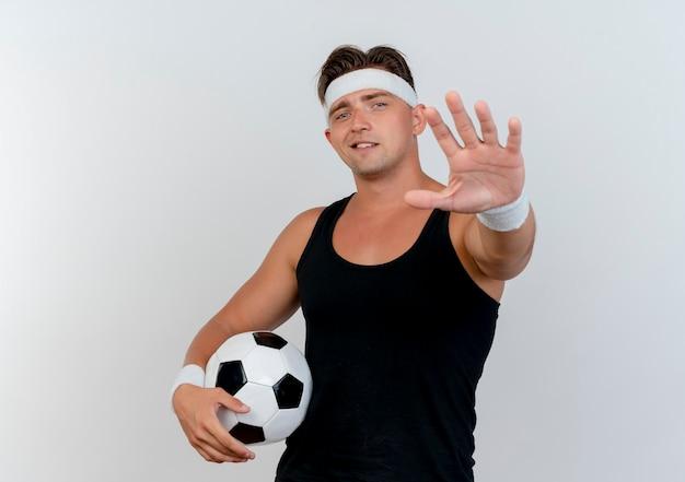 Tevreden jonge knappe sportieve man met hoofdband en polsbandjes die voetbal houden en hand uitstrekken naar voren geïsoleerd op een witte muur