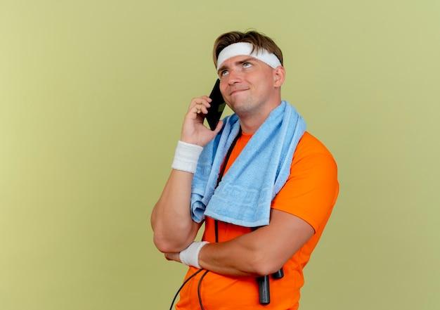 Tevreden jonge knappe sportieve man met hoofdband en polsbandjes met handdoek en springtouw om nek opzoeken en praten aan de telefoon kijken geïsoleerd op olijfgroene muur