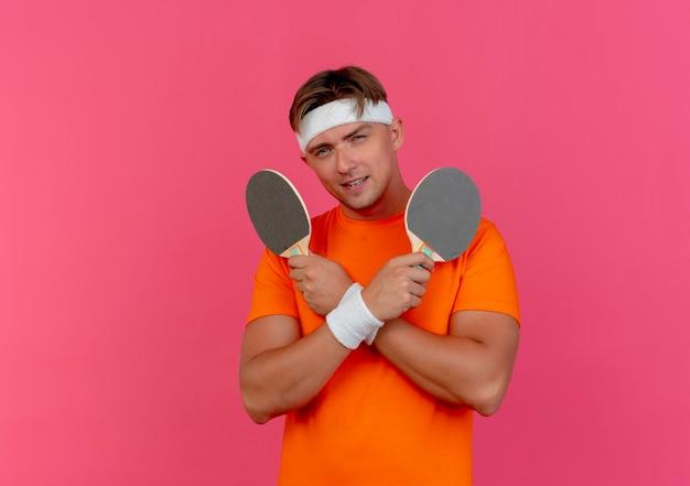Tevreden jonge knappe sportieve man met hoofdband en polsbandjes met pingpongrackets geïsoleerd op roze muur
