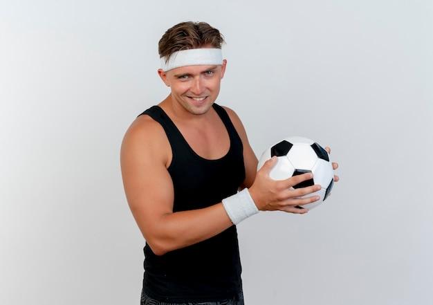 Tevreden jonge knappe sportieve man met hoofdband en polsbandjes met voetbal geïsoleerd op een witte muur