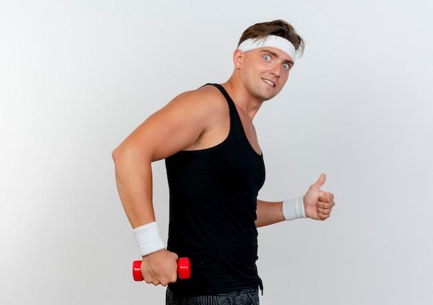 Tevreden jonge knappe sportieve man met hoofdband en polsbandjes staande in profielweergave met halter en duim opdagen geïsoleerd op witte muur