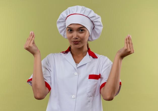 Tevreden jonge kokvrouw die eenvormige chef-kok draagt die uiteindegebaar op geïsoleerde groene muur toont