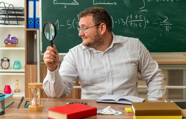 Tevreden jonge leraar met een bril die aan het bureau zit met schoolbenodigdheden in de klas en door een vergrootglas naar de zijkant kijkt Gratis Foto