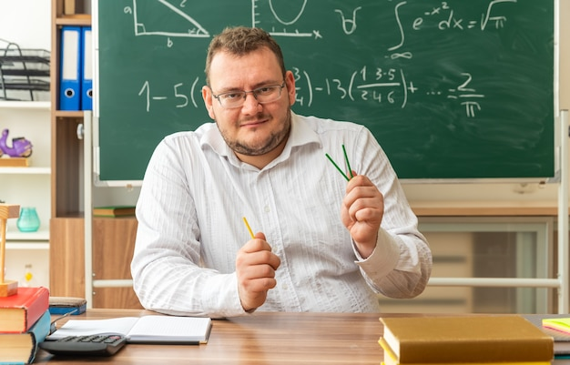 Tevreden jonge leraar met een bril die aan het bureau zit met schoolbenodigdheden in de klas met telstokken die naar voren kijken