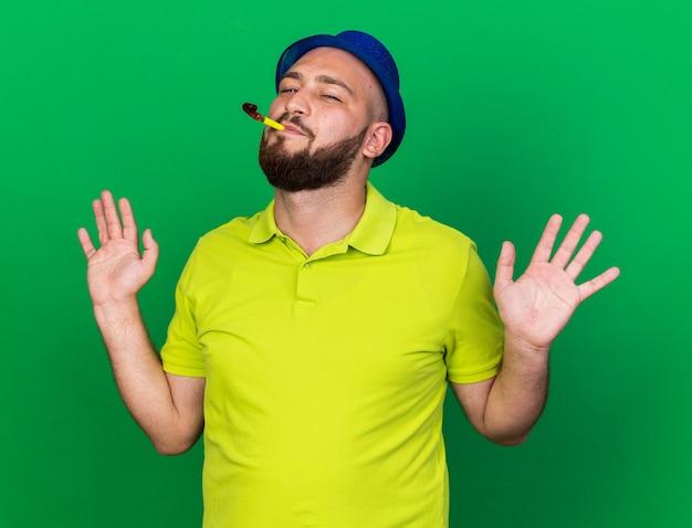 Tevreden jonge man met een blauwe feestmuts die een feestfluitje blaast en de handen spreidt